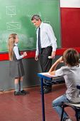 Little schoolgirl and male teacher looking at each other standing by greenboard in classroom