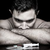 stock photo of syringe  - Grunge image of a depressed drug addict looking at a syringe and drugs - JPG