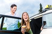 Young businesswoman gets out of taxi, she holding a cup of coffee