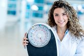 Female nutritionist at the hospital holding a weight scale