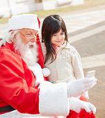 Cute girl and Santa Claus taking selfportrait through smartphone in courtyard