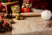 A Christmas Still Life with an old parchment scroll, presents, ornaments and a Santa Hat. Closeup in