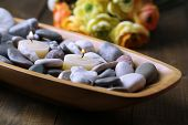 Wooden bowl with spa stones and candles on wooden background