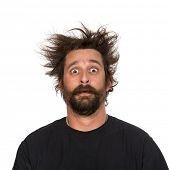 Goofy young man, with full beard and moustache and wild hair, pull a comical face to the camera Studio portrait over white Space for your text