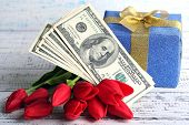 Gift box with money and flowers on color wooden background