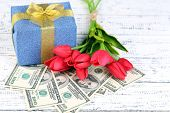 Gift boxes with money and flowers on color wooden background