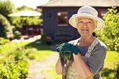 image of shovel  - Portrait of senior woman wearing hat with gardening tools outdoors - JPG