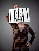 stock photo of jail  - Woman holding a paper with a prisoner in jail behind the bars on it in front of her head - JPG