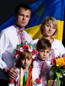 Proud family in the Ukrainian national costumes with Ukrainian flag