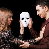 Fashion Happy Couple In Love Holding A White Mask Face. Psychological Concept. Duality Look At Relat