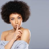 Beautiful African American woman with a large afro hairdo making a hushing gesture holding her finger to her lips as she requests silence, with copyspace