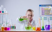 Funny young chemist pouring reagent into flask
