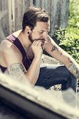stock photo of redneck  - A redneck sitting outside a abandoned house and smoke cigarettes - JPG