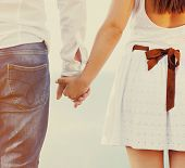 stock photo of suspenders  - Happy couple in love holding hands walking away near the sea - JPG