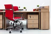 desks and red armchairs on a white wall