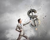 pic of karate  - Businessman breaking stone dollar symbol with karate punch - JPG