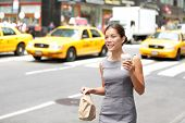 Business woman in New York City candid and real. Businesswoman in Manhattan walking in dress suit ho