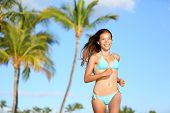 Bikini woman running on beach smiling happy and on tropical summer beach with palm trees. Beautiful sexy mixed race Asian Caucasian girl in her 20s. Image from Hawaii.