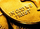 Pile of gold coins and bullion with dark background and words In God We Trust