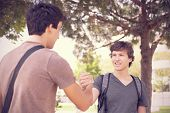 Happy young student giving a handshake to his classmate (selective focus)