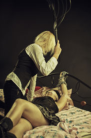 stock photo of scourge  - Domination and sex games with lash in a bedroom - JPG