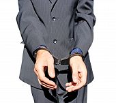 Man In Black Suit In Handcuffs On His Hands Isolated