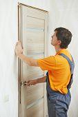 Male handyman carpenter at interior wood door installation
