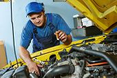 auto mechanic repairman tighten screw with spanner during automobile car maintenance at engine repai