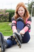 Teenage Girl Putting On Rollerblades