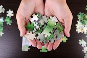 Puzzle piece in hands on wooden table background