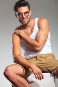 sexy casual fit man smiling and holding his hand on shoulder, sitting in studio