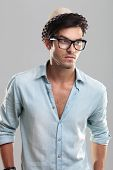 Handsome man in blue shirt, wearing glasses, on gray background