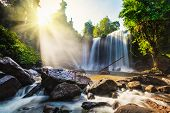 Tropical waterfall with sun rays in Cambodia