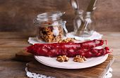 Tasty oriental sweets (churchkhela) and fresh nuts, on wooden background