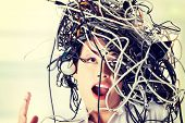 Troubled shocked businesswoman with cables on head