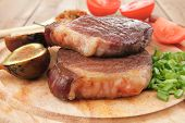 meat savory : grilled beefsteak served with hot cayenne peppers green stuff sweet figs and cutlery o
