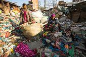 KATHMANDU, NEPAL - DEC 22, 2013: Unidentified people from poorer areas working in sorting of plastic