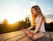 Girl meditating outdoors. Child practicing yoga