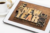 Happy New Year 2015 greetings  - text in vintage letterpress wood type blocks on a digital tablet with a cup of coffee