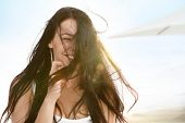 image of windswept  - Happy young woman standing in the wind - JPG