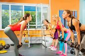 Instructor, young women exercising with dumbbells