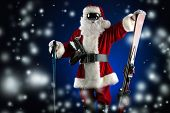 Santa Claus is standing in the ski mask and holding a skiing. Christmas.