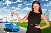 Woman with car key in hand. Small automobile on road
