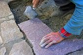 Senior Landscape Gardener Fitting A Flagstone Tile With A Rubber Mallet