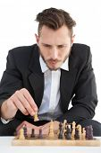 Focused businessman playing chess solo on white background