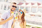 A picture of a joyful couple eating ice-cream cones in the city