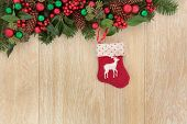 Christmas eve abstract border with stocking decoration, holly, red baubles, mistletoe and winter greenery over light oak background.