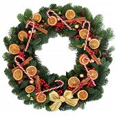 Christmas and winter wreath with dried  fruit, cinnamon spice, bauble decorations and winter greenery background.
