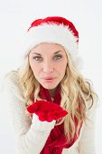 Portrait of young woman wearing santa hat as she blows kiss over white background
