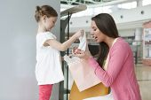 Mother giving daughter gift from paper shopping bag